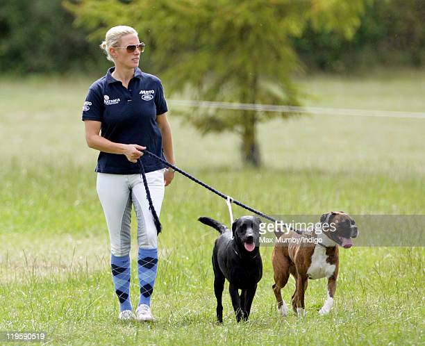 Zara Phillips walks her dogs around the cross country course during a break from competing in the AstonleWalls Horse Trials on July 22 2011 in...