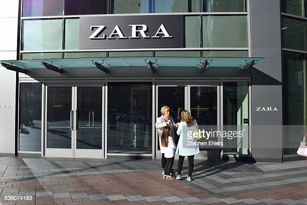 A Zara storefront and sign in downtown Seattle Washington Some shoppers were talking on the sidewalk outside the entrance