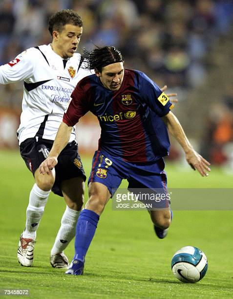 Barcelonas Argentinian Lionelm Messi vies for the ball with Argentinian Andres Dalesandro during their Spanish king cup football match at Romareda...