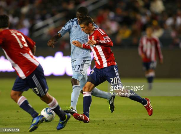 Zarek Valentin of Chivas USA and CJ Sapong of Sporting Kansas City vie for the ball during the MLS match at The Home Depot Center on March 19 2011 in...