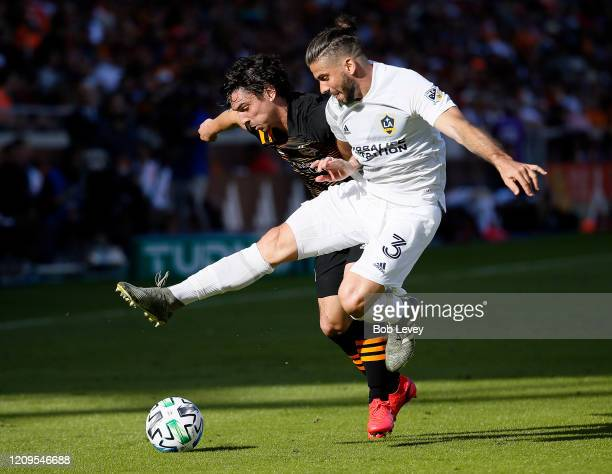 Zarek Valentin of Houston Dynamo and Emilano Insua of Los Angeles Galaxy battle for the ball during the second half at BBVA Stadium on February 29...