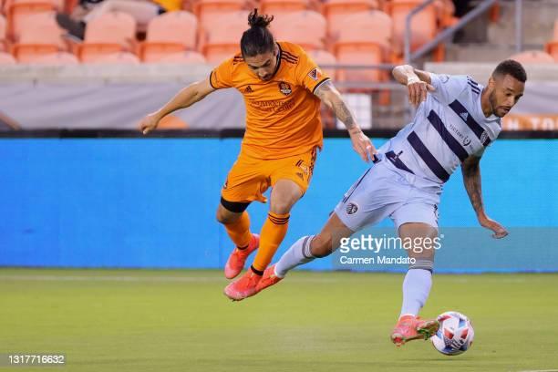 Zarek Valentin of Houston Dynamo battles for ball control against Khiry Shelton of Sporting Kansas City during the second half at BBVA Stadium on May...