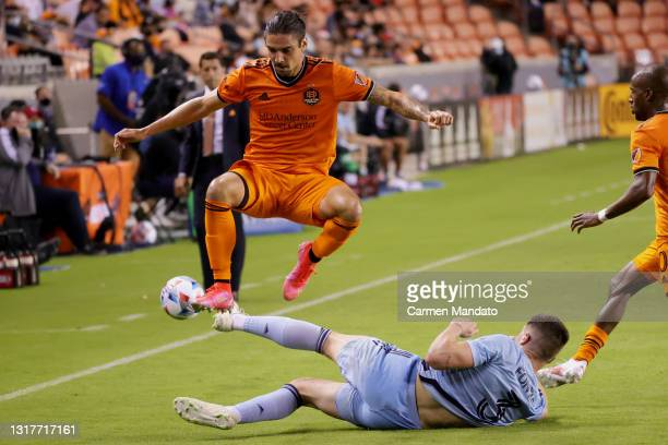 Zarek Valentin of Houston Dynamo jumps over Andreu Fontas of Sporting Kansas City during the second half at BBVA Stadium on May 12, 2021 in Houston,...