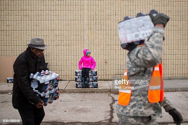 Zariah Garner age 9 of Flint rests on a stack of water as national guard members and civilians carry cases to vehicles on January 23 2016 in Flint...