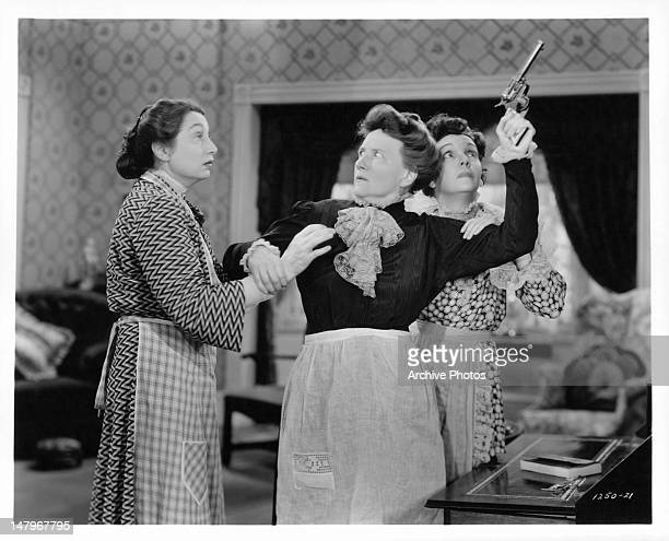 Zasu Pitts and Aline MacMahon holding onto Marjorie Main as she raises gun to the ceiling in a scene from the film 'Tish' 1942