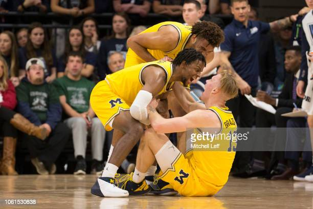 Zavier Simpson and Isaiah Livers of the Michigan Wolverines celebrate with Ignas Brazdeikis after Brazdeikis made a basket and was fouled in the...