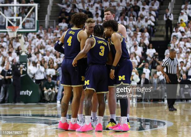 Zavier Simpson of the Michigan Wolverines and his teammates prepare prior to the game against the Michigan State Spartans at Breslin Center on March...