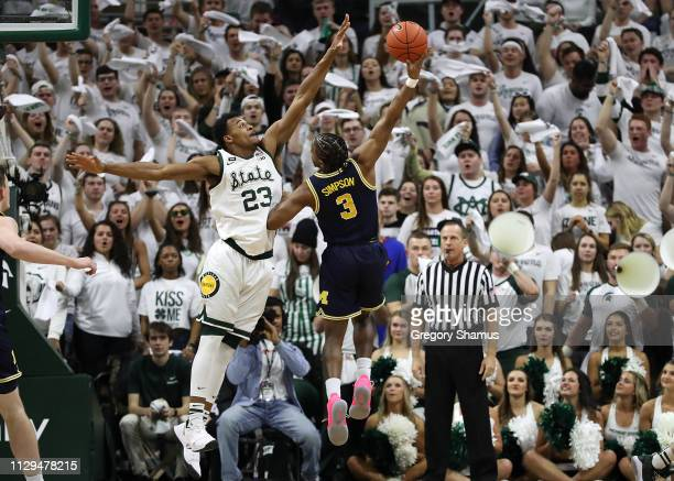 Zavier Simpson of the Michigan Wolverines attempts a shot around Xavier Tillman of the Michigan State Spartans during the first half at Breslin...