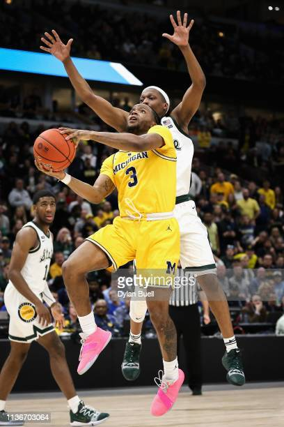 Zavier Simpson of the Michigan Wolverines attempts a shot while being guarded by Cassius Winston of the Michigan State Spartans in the second half...