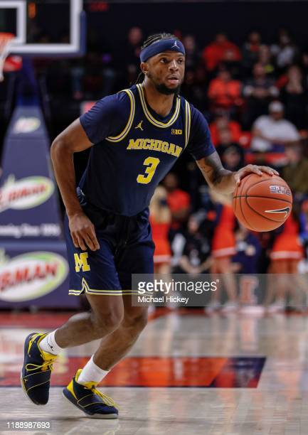 Zavier Simpson of the Michigan Wolverines brings the ball up court during the game against the Illinois Fighting Illini at State Farm Center on...