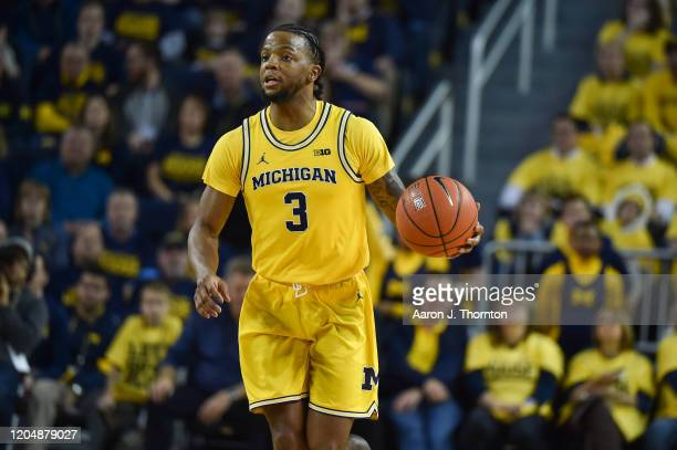 Zavier Simpson of the Michigan Wolverines brings the ball up court during the first half of a college basketball game against the Ohio State Buckeyes...