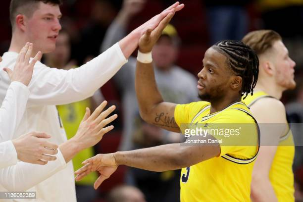 Zavier Simpson of the Michigan Wolverines celebrates with Jon Teske in the second half against the Iowa Hawkeyes during the quarterfinals of the Big...