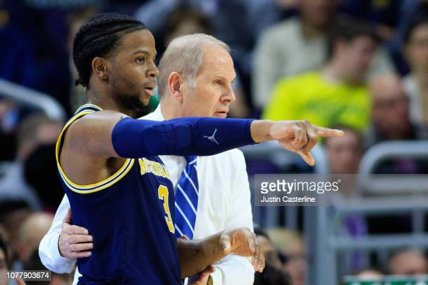 Zavier Simpson of the Michigan Wolverines discusses a play with Head coach John Beilein of the Michigan Wolverines in the game against the...