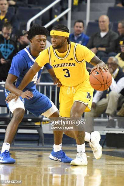 Zavier Simpson of the Michigan Wolverines dribbles around Shereef Mitchell of the Creighton Bluejays during a basketball game at the Crisler Center...