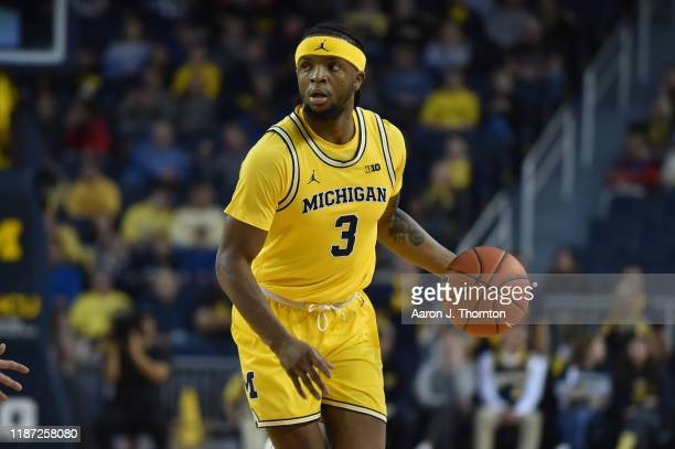 Zavier Simpson of the Michigan Wolverines dribbles the ball during a college basketball game against the Creighton Bluejays at Crisler Arena on...