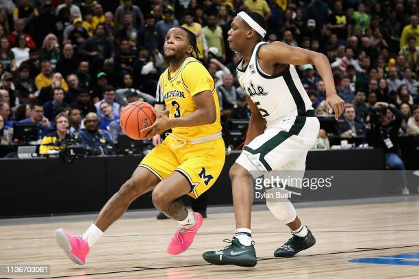 Zavier Simpson of the Michigan Wolverines dribbles the ball while being guarded by Cassius Winston of the Michigan State Spartans in the second half...