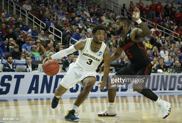 Zavier Simpson of the Michigan Wolverines drives against Corey Davis Jr #5 of the Houston Cougars in the second half during the second round of the...