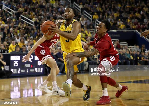 Zavier Simpson of the Michigan Wolverines drives between Devonte Green and Zach McRoberts of the Indiana Hoosiers during the first half at Crisler...