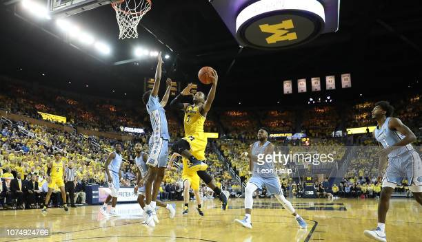 Zavier Simpson of the Michigan Wolverines drives the ball to the basket as Brandon Robinson of the North Carolina Tar Heels defends during the second...