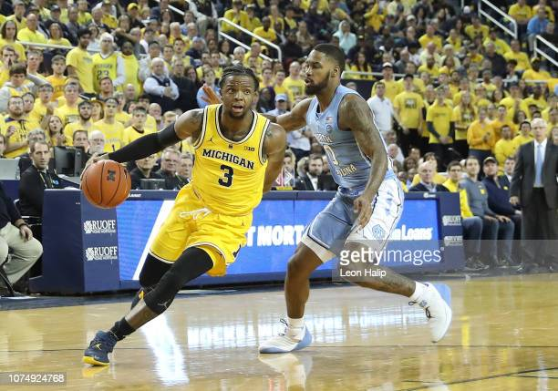 Zavier Simpson of the Michigan Wolverines drives the ball to the basket as Seventh Woods of the North Carolina Tar Heels defends during the second...