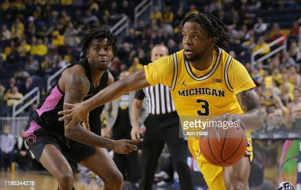Zavier Simpson of the Michigan Wolverines drives the ball to the basket as Jamari Wheeler of the Penn State Nittany Lions defends during the first...