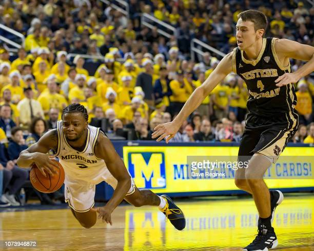Zavier Simpson of the Michigan Wolverines drives to the basket and is tripped up by Jared Printy of the Western Michigan Broncos at Crisler Arena on...