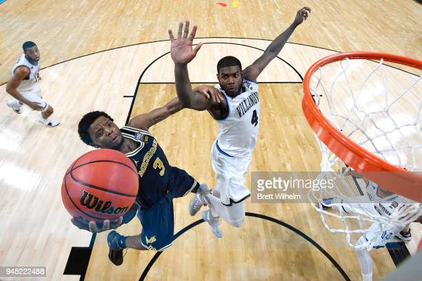 Zavier Simpson of the Michigan Wolverines drives to the basket against Eric Paschall of the Villanova Wildcats during the second half of the 2018...