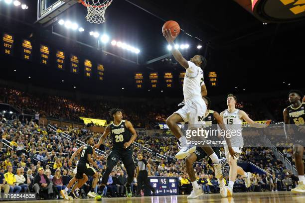 Zavier Simpson of the Michigan Wolverines drives to the basket past Eric Hunter Jr. #2 of the Purdue Boilermakers during the first half at Crisler...