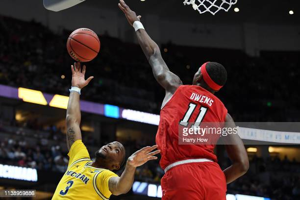 Zavier Simpson of the Michigan Wolverines drives to the basket against Tariq Owens of the Texas Tech Red Raiders during the 2019 NCAA Men's...