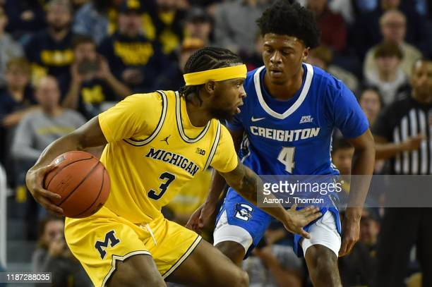 Zavier Simpson of the Michigan Wolverines looks to pass while defended by Shereef Mitchell of the Creighton Bluejays during the second half of a...