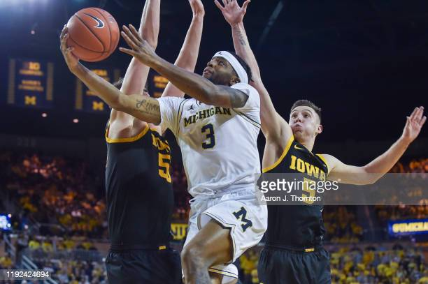 Zavier Simpson of the Michigan Wolverines looks to score against Luke Garza and C.J. Fredrick of the Iowa Hawkeyes during the second half of a...