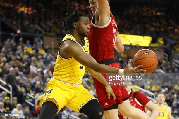 Zavier Simpson of the Michigan Wolverines passes around Tanner Borchardt of the Nebraska Cornhuskers during the first half at Crisler Arena on...