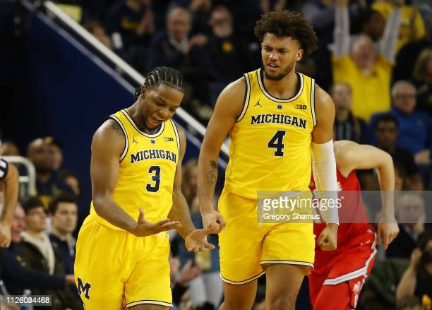 Zavier Simpson of the Michigan Wolverines reacts after a three point basket next to Isaiah Livers while playing the Ohio State Buckeyes at Crisler...