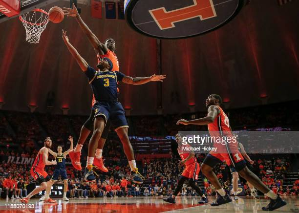 Zavier Simpson of the Michigan Wolverines shoots the ball against Kofi Cockburn of the Illinois Fighting Illini during the second half at State Farm...