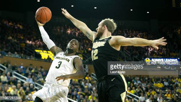 Zavier Simpson of the Michigan Wolverines shoots the ball as Evan Boudreaux of the Purdue Boilermakers defends during the second half of the game at...