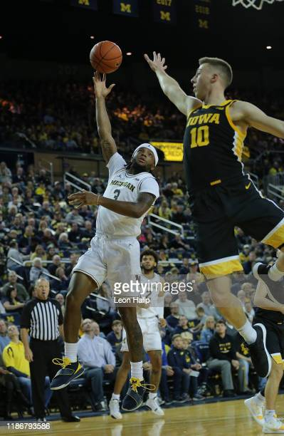 Zavier Simpson of the Michigan Wolverines shoots the ball over Joe Wieskamp of the Iowa Hawkeyes during the first half of the game at Crisler Center...