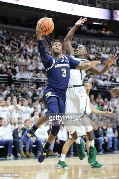 Zavier Simpson of the Michigan Wolverines shoots the ball while defended by Lourawls Nairn Jr #11 of the Michigan State Spartansat Breslin Center on...