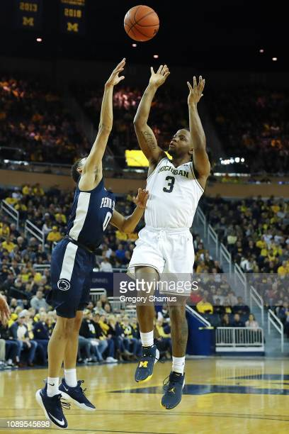 Zavier Simpson of the Michigan Wolverines takes a shot over Myreon Jones of the Penn State Nittany Lions during the first half at Crisler Arena on...