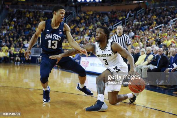 Zavier Simpson of the Michigan Wolverines tries to drive around Rasir Bolton of the Penn State Nittany Lions during the first half at Crisler Arena...