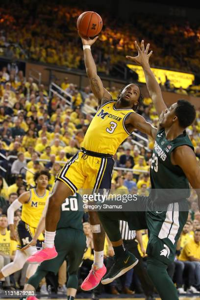 Zavier Simpson of the Michigan Wolverines tries to get a first half shot over Xavier Tillman of the Michigan State Spartans at Crisler Arena on...