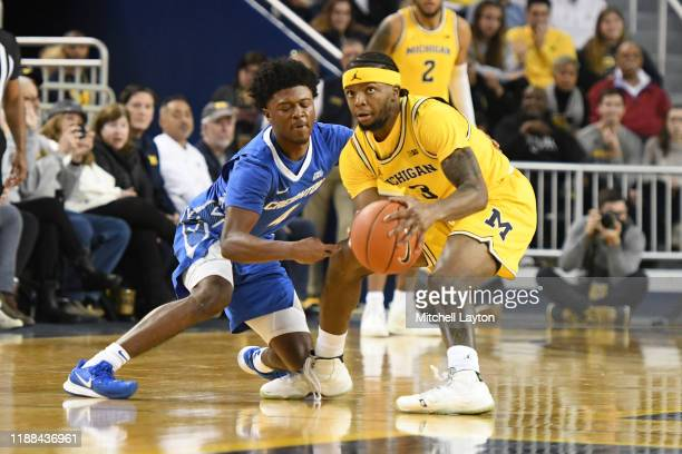 Zavier Simpson of the Michigan Wolverines tries to get around Shereef Mitchell of the Creighton Bluejays during a basketball game at the Crisler...