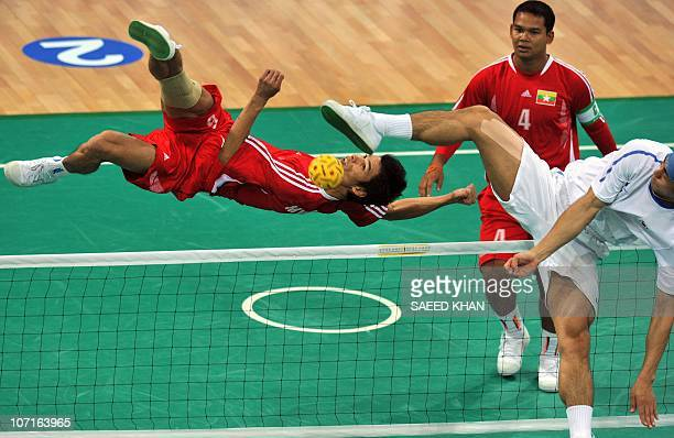 Zaw lat of Myanmar returns the Takraw to Lee JunHo of South Korea during the men's double Sepaktakraw final match at the Haizhu sports stadium in...