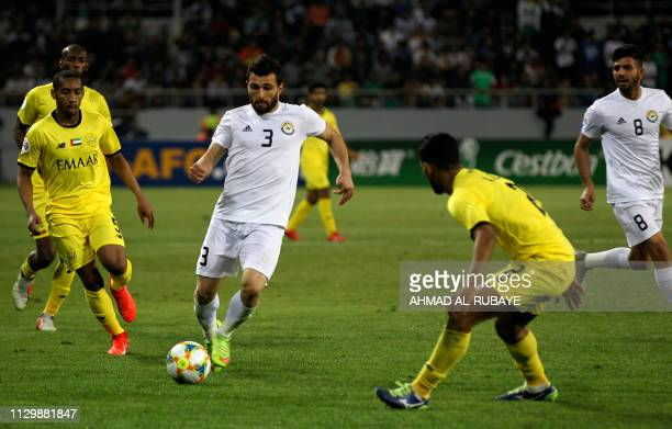Zawraa's defender Hussein Jwayed is marked by Wasl's defender Abdurahman Ali during the AFC champions league Group A football match between Iraq's Al...