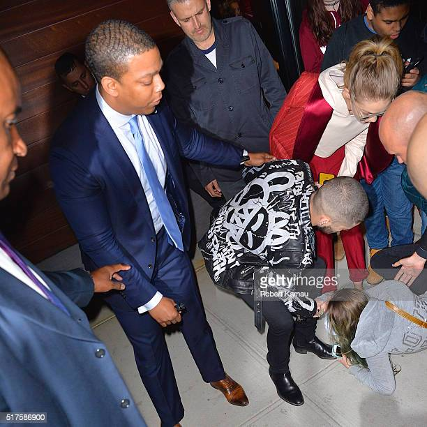 Zayn Malik and girlfriend supermodel Gigi Hadid help a fan that fainted after seeing the couple leaving their East Village apartment on March 25 2016...