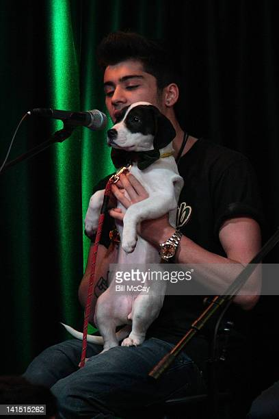 Zayn Malik from the band One Direction performs with a puppy from the Delco SPCA at Radio Station Q102 iHeartRadiod Performance Theater March 17 2012...