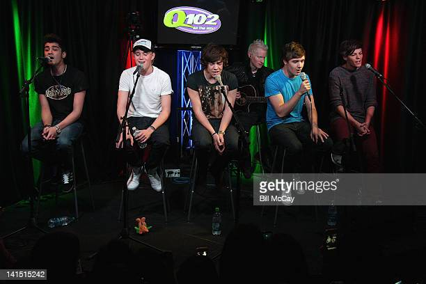 Zayn Malik, Niall Horan, Harry Styles, guitar player Aron Forbes, Liam Payne and Louis Tomlinson from the band One Direction perform with puppies...