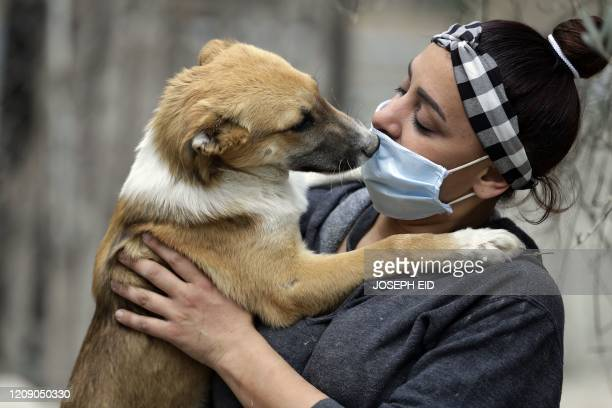 Zaynab Razzouk, head of the animal protection NGO Carma, plays with a dog at the shelter in the area of Koura, north of the Lebanese capital Beirut...