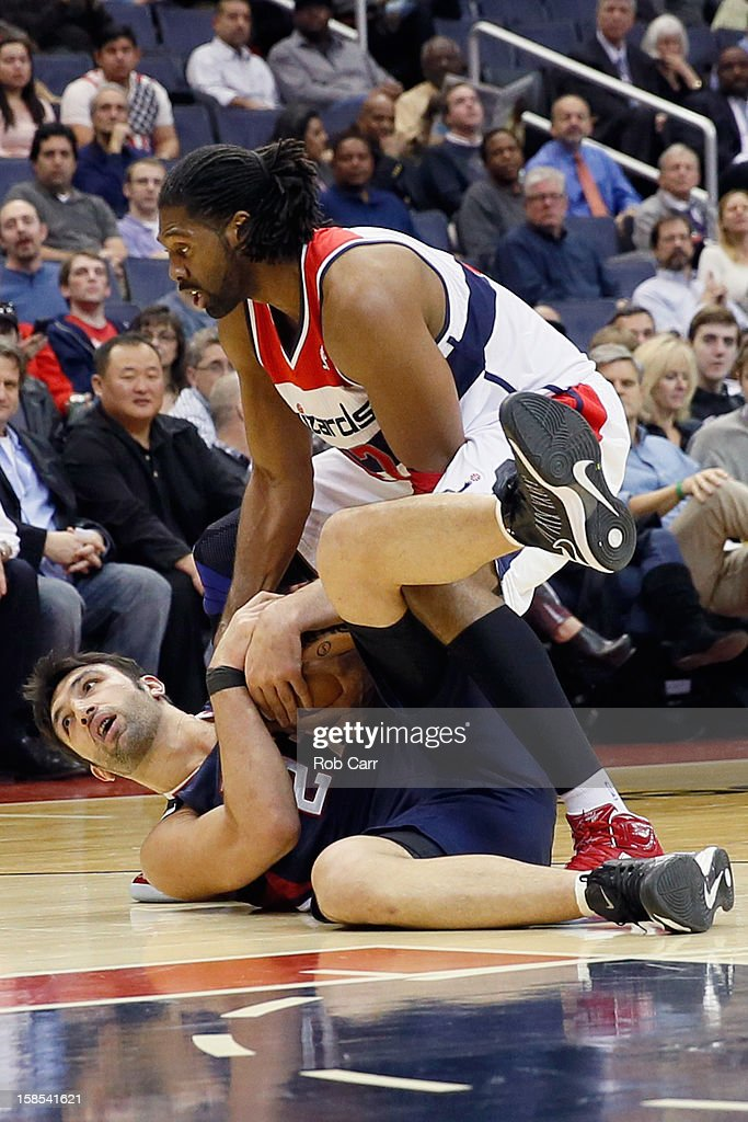 Zaza Pachulia #27 of the Atlanta Hawks and Nenê #42 of the Washington Wizards go after a loose ball during the first half at Verizon Center on December 18, 2012 in Washington, DC.