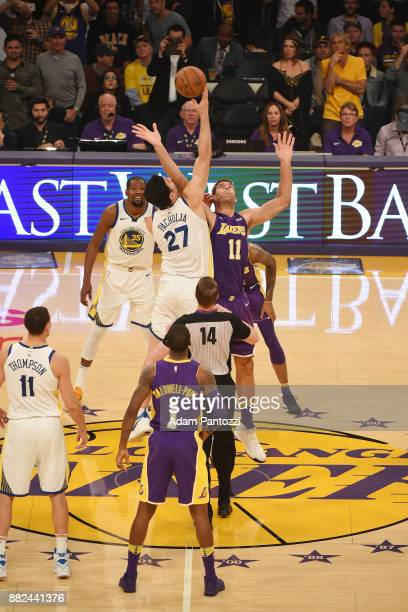 Zaza Pachulia of the Golden State Warriors and Brook Lopez of the Los Angeles Lakers tipoff at the beginning of the game on November 29 2017 at...