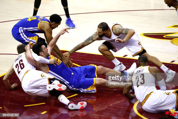 Zaza Pachulia of the Golden State Warriors gets tangled with Kyle Korver and Deron Williams of the Cleveland Cavaliers in the third quarter in Game 4...
